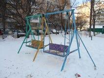 Färgrika barns gungor i snön parkerar område av ‹för †staden Royaltyfri Fotografi