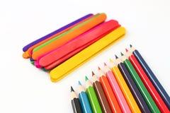Färgrika blyertspennafärgpennor över en vit bakgrund Arkivfoton