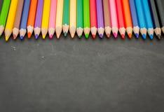 Färgrika blyertspennafärgpennor på en svart tavlabakgrund Royaltyfria Foton