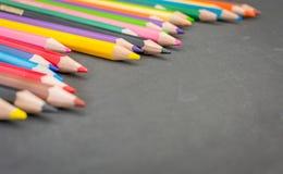 Färgrika blyertspennafärgpennor på en svart tavlabakgrund Royaltyfri Foto