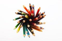 Färgrika blyertspennor i en blyertspennaask på en vit bakgrund arkivfoton