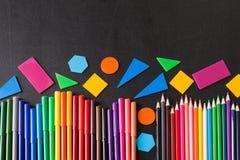 Färgrika blyertspennor i rad och geometriska diagram på den svarta svart tavlan för skola Royaltyfria Bilder