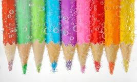 Färgrika blyertspennor i vatten med bubblor Royaltyfria Foton