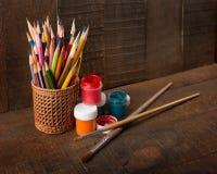 Färgrika blyertspennor, målarfärger och konstnärborstar Royaltyfri Bild