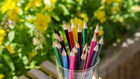 Färgrika blyertspennor med blommabakgrunder Arkivbild