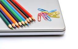 Färgrika blyertspennor med det pappers- stiftet på bärbara datorn Arkivfoto