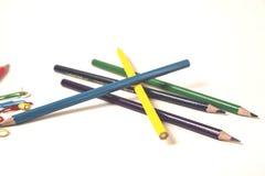 Färgrika blyertspennor med paperclips på det vita skrivbordet royaltyfri fotografi