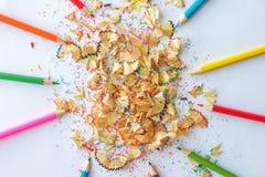 Färgrika blyertspennor och träshavings från blyertspennor Royaltyfri Bild