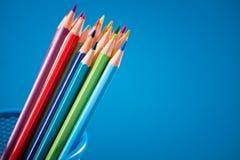 Färgrika blyertspennor på blå bakgrund Arkivbilder