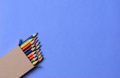 Färgrika blyertspennor på blått Royaltyfri Bild