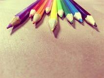 Färgrika blyertspennor på brun bakgrund Arkivfoto