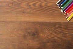 Färgrika blyertspennor på den bruna trätabellbakgrunden Ram av kulöra blyertspennor över trä med fritt utrymme för text Arkivfoto