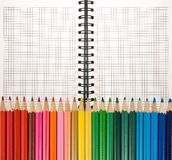 färgrika blyertspennor på en anteckningsbok royaltyfri foto