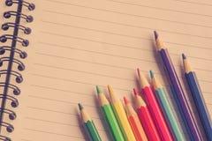 Färgrika blyertspennor på linjärt papper royaltyfri foto