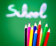 Färgrika blyertspennor på svart tavlabakgrund Royaltyfria Bilder