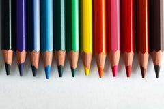 Färgrika blyertspennor som är ordnade som en färgpallete på papper Royaltyfri Bild