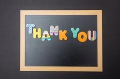 Färgrika bokstäver som formar ordet för att tacka dig på svart tavla med träramen, svart väggbakgrund royaltyfria foton