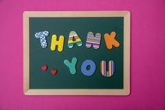 Färgrika bokstäver som formar ordet, tackar dig på grönt bräde med träramen, rosa väggbakgrund royaltyfria bilder