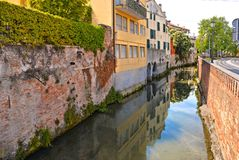 Färgrika byggnader, arkitektur, vattenreflexioner på stadskanalen och gammal fasad med blå himmel i Padua Veneto, Italien arkivfoton