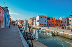 Färgrika byggnader, folk och fartyg framme av en kanal på Burano Arkivfoto