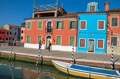 Färgrika byggnader, folk och fartyg framme av en kanal på Burano Arkivbild