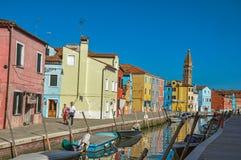 Färgrika byggnader, torn, folk och fartyg framme av en kanal på Burano Royaltyfri Foto