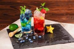 Färgrika coctailar med mintkaramellen, limefrukt, is, bär och carambolaen på träbakgrunden Uppfriskande sommardrycker kopiera avs Arkivbilder