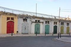Färgrika dörrar av lagringar i tom gata av Malta arkivbilder