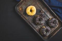 Färgrika donuts på den svarta tabellen Top besk?dar arkivbilder