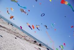 Färgrika drakar över strand Arkivbild