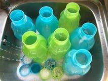 Färgrika dricka plast- flaskor är den influtna köktvättställen royaltyfri foto