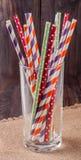 Färgrika dricka randiga sugrör i exponeringsglas på en trätabell med att plundra Royaltyfri Fotografi
