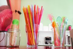 Färgrika dricka sugrör i exponeringsglas, plast- sked och plast-spatel bearbetar kitchenware för glass Royaltyfria Bilder