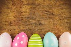 Färgrika easter ägg framme av en gammal träbakgrund arkivfoto