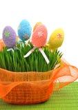 Färgrika easter ägg i blomsterrabatten med grönt nytt gräs Arkivbilder