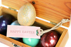Färgrika easter ägg i den wood asken med lyckliga easter smsar på papper Royaltyfri Foto