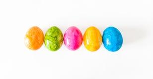 Färgrika easter ägg i rad och vit bakgrund Royaltyfri Fotografi