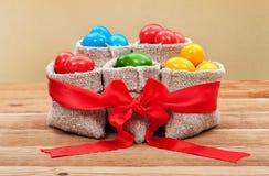 Färgrika easter ägg i säckvävpåsar - festlig ordning Royaltyfri Bild