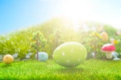Färgrika easter ägg och ett stort grönt easter ägg på grönt gräs för vår Royaltyfria Foton