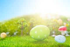 Färgrika easter ägg och ett stort grönt easter ägg på grönt gräs för vår Arkivbilder