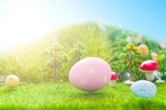 Färgrika easter ägg och ett stort rosa easter ägg på grönt gräs för vår Arkivbilder