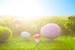 Färgrika easter ägg och ett stort rosa easter ägg på grönt gräs för vår Royaltyfri Fotografi