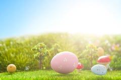 Färgrika easter ägg och ett stort rosa easter ägg på grönt gräs för vår Royaltyfri Foto