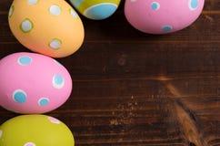 Färgrika easter ägg på en träbakgrund Fotografering för Bildbyråer