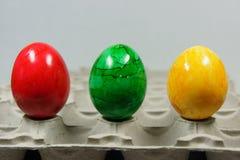 Färgrika easter ägg på ett äggmagasin Arkivfoto