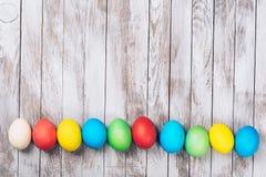 Färgrika easter ägg på träbakgrund Utrymme för text kort easter Royaltyfri Foto