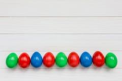 Färgrika easter ägg på vitträbakgrund Arkivfoto