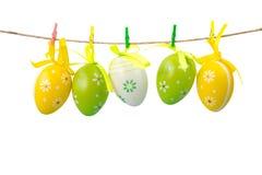 Färgrika easter ägg som hänger på ett rep som isoleras på vit bakgrund Royaltyfri Bild