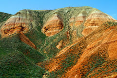 Färgrika eroderade klippor med den gröna gräs- lutningen royaltyfri fotografi