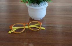 Färgrika exponeringsglas och vit blomkruka på trätabellbakgrund Arkivfoto